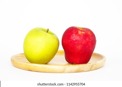 Two apples, different in color placed on a wooden plate over a white background, showing its color and shape.  The fruit is edible, and it has a significant meaning in Christian tradition