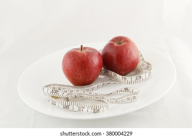 Two apples with a measuring tape in a white plate