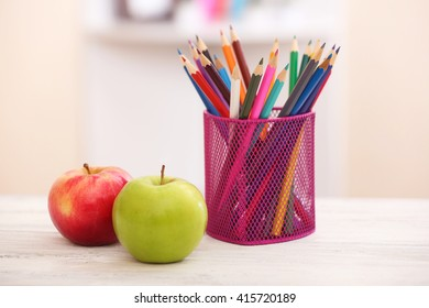 Two apples and organizer with pencils on table in the room