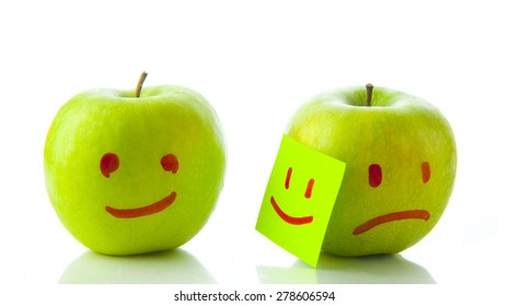 Two apples smiling and crying on white background. Concept of hypocrisy to hide feelings of emotion hold your sadness joy couples in romantic relationships and pair family