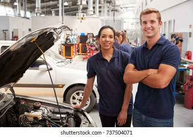 Two apprentice mechanics looking to camera beside a car