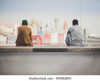 Two arab construction workers taking brake and sitting on the sidewalk in Dubai, United Arab Emirates