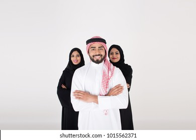 Two arab females with one male smiling and standing on white background