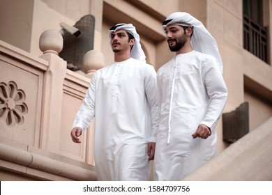 two arab man waering traditional clothes and walking in downtown