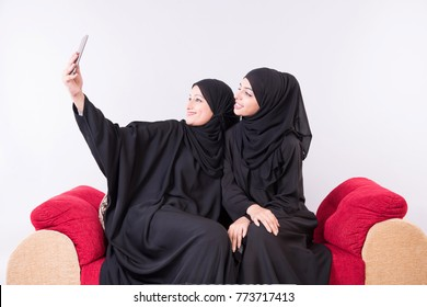 two Arab women taking slefie at home with white background