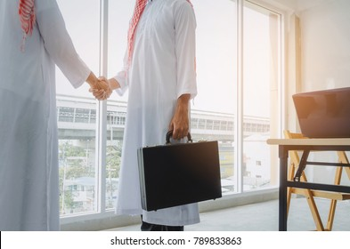 two Arabian business man transfer deal after finishing up a business meeting in office, handover of briefcase in hand of partner, successful, meeting, partner, teamwork, community, connection concept