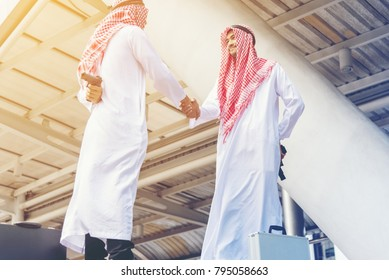 Two Arabian Businessman shaking hand after discussed while other people holding gun in hands double-cross ,blackmail business concept