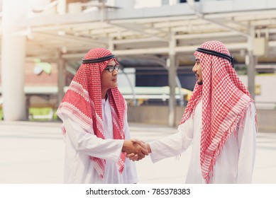 Two  Arabian businessman smile and shaking hands after meeting and over deal their agreement to sign agreement or contract.