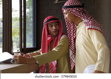 Two Arabian men is discussing together.
