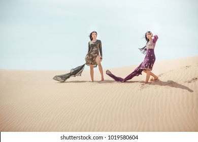 Two arabian women in national clothes travelling in desert. Copy space landscape of sand dunes and blue sky. Creative art fashion shot travel concept.
