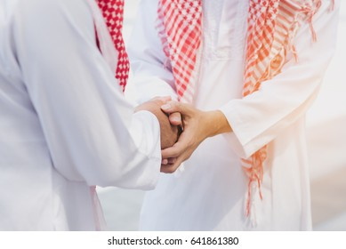 Two Arabic men having warm meeting with a hug and handshakes, modern city background