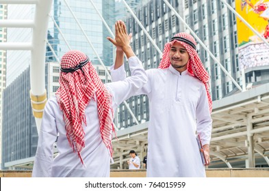 Two Arabic muslim wear white shirt humble say hello in the morning on cityscape background,