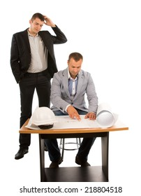 Two architects or builders working on a plan as a team trying to solve a problem with one seated at a table and the other standing scratching his head, isolated on white