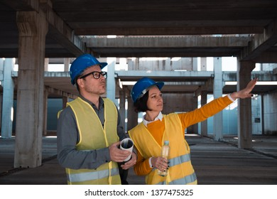 Two architects discussing over blueprint