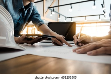 Two Architects engineer discussing  data working and tablet, laptop with blueprint - Closeup on hands and project print.