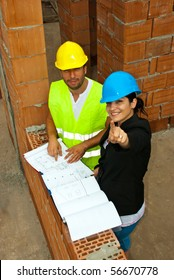 Two architects in a house under construction having a discussion and the woman pointing up to you