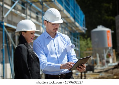Two architects a man and a woman in construction in white helmets