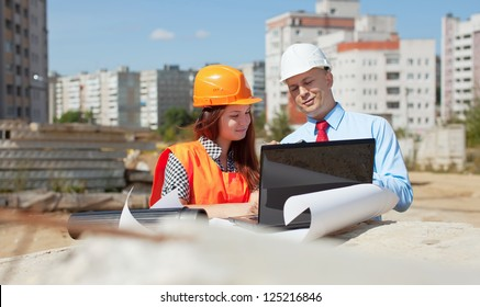 Two architects wearing protective helmet standing in front of building site