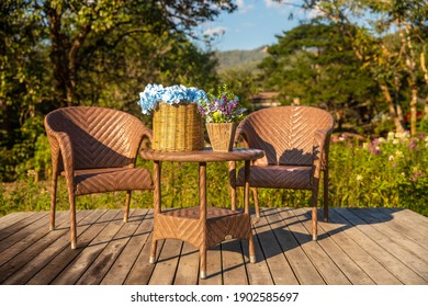 Two armchairs, wooden garden furniture on wood floor  outdoor for relaxing on hot summer days. Garden landscape with two chairs in nature, flowers in vase and cat. Rest in park cafe. Backyard exterior