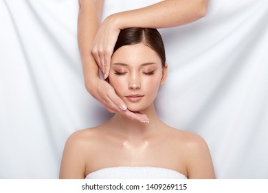 two arms doing massage for beautiful woman on white, fresh and healthy girl's face in spa, female having relaxation