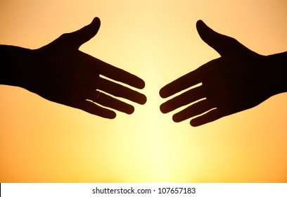 two arms stretching towards each other to shake against the sunset