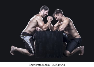 Two armwrestlers, have an arm wrestling match on a black box shirtless