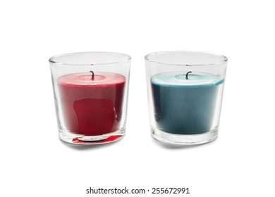 Two aromatic candles in glass candlesticks on white background