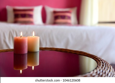 Two aromatic candles on a glass table. Bedroom interior. A cozy romantic atmosphere.