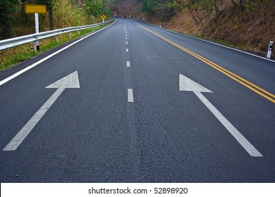 Two arrow on a black road.