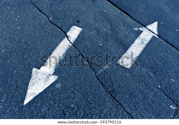 Two arrows on blue toned cracked asphalt surface. Urban background.