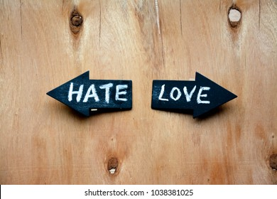 Two arrows with words hate and love on rustic wooden table
