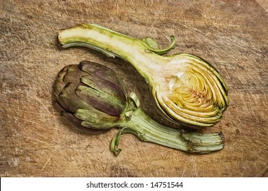 Two artichokes on a wooden cutting table.