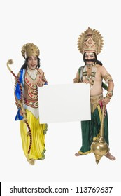 Two artists dressed-up as Rama and Ravana and holding a blank card