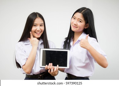two asia thai high school student uniform Best friends beautiful girl using her tablet and funny