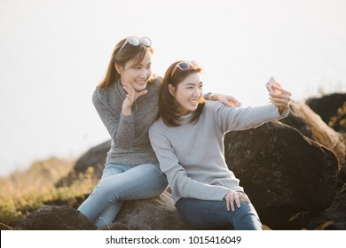 two Asia woman Friends taking selfie at a national park