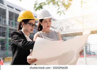 Two asian architect girl wearing helmat looking at the building plan. At a construction site.