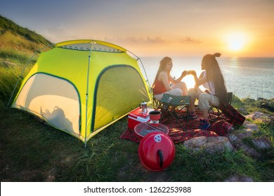 Two Asian beautiful girls Outdoor camping on the mountain next to the sea .