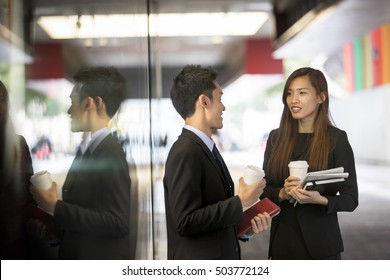 Two Asian Business colleagues talking outside in modern Asian city.