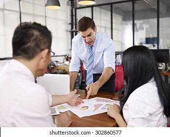 two asian business executives arguing with caucasian superior in office of a multinational company.