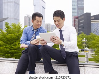 two asian business executives using ipad in city park.