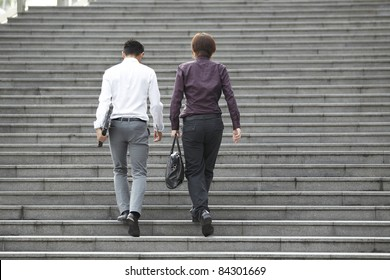 Two Asian Business men walking on stairs
