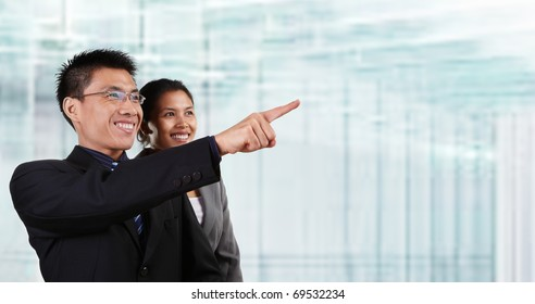 Two Asian business people pose together and the male pointing away his hand, with blur glass windows as background