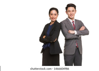 Two Asian business people standing and posing, woman crossed her arms, man putting hand in pants's bag, isolated on white background copy space on left side.