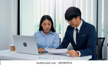 Two asian business people are working together and analyzing the data on the computer.