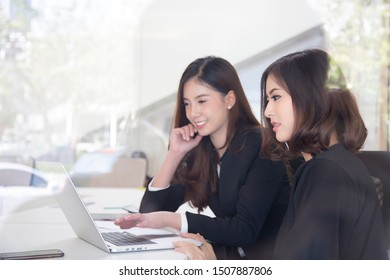 Two asian business woman discuss her project in the office.
