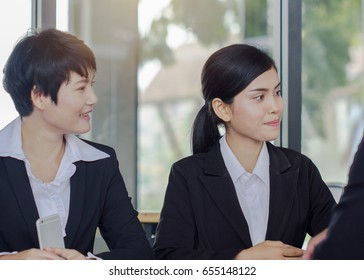 Two asian business woman smiling in conference room.