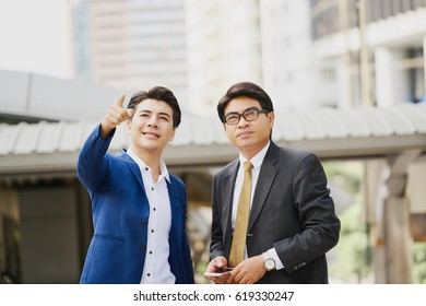 Two asian businessman pointing and looking something while talking and holding smartphone at outside office against the modern building
