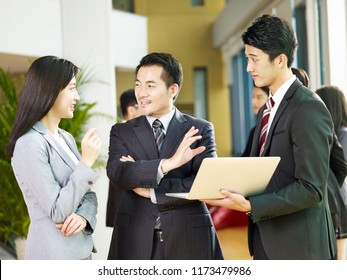 two asian businessmen and a businesswoman discussing business using laptop computer in company lobby.