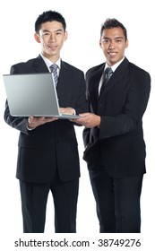 Two Asian businessmen, Chinese and Malay, holding a laptop together signifying racial harmony and international, regional cooperation in Asia.  Both wearing suit, tie, shirt, formal wear.