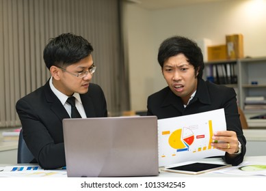 Two asian businessmen discuss about business of company,Two people are talking about work stress and more serious.